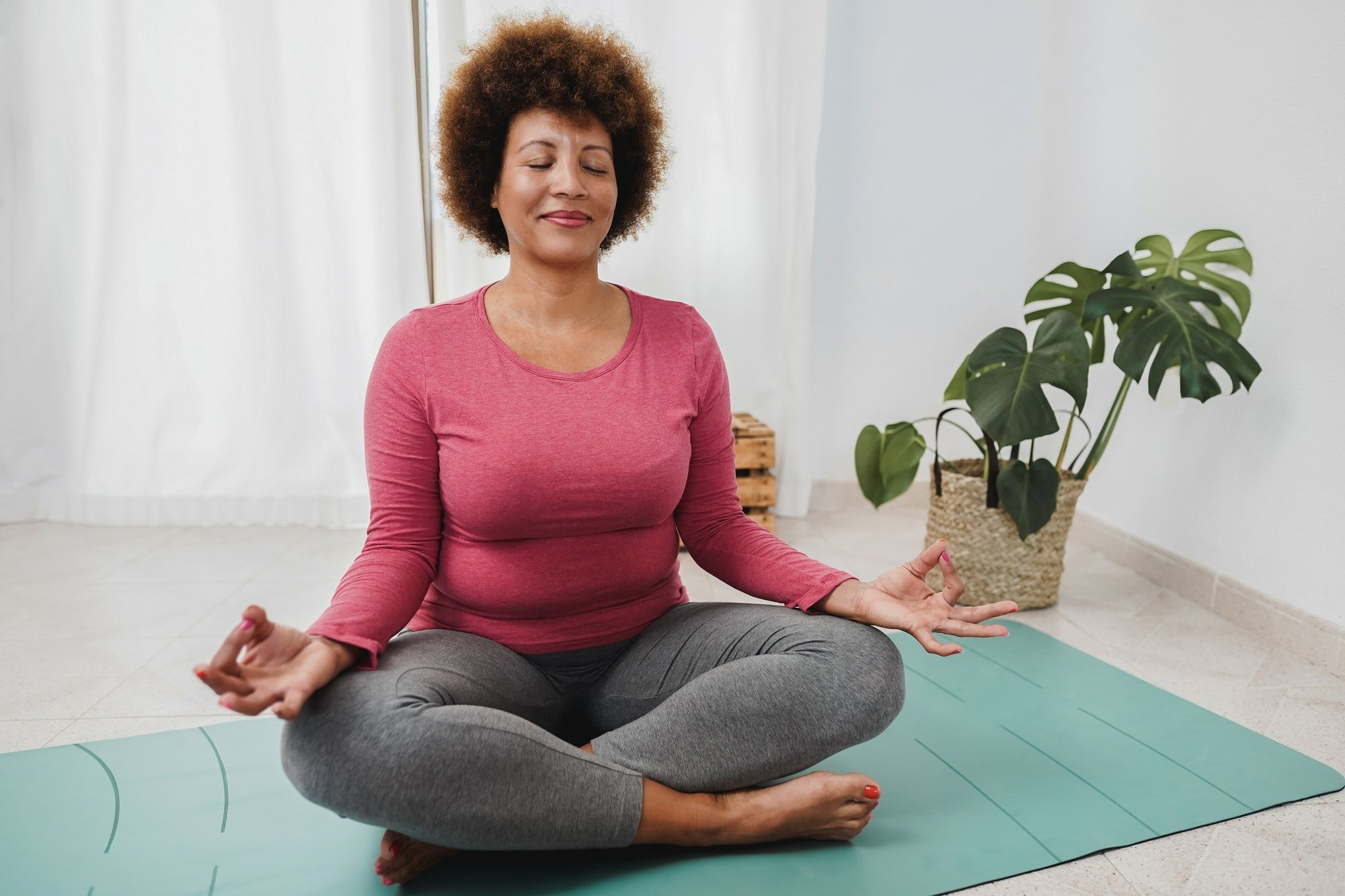African senior woman doing yoga session at home - Focus on face