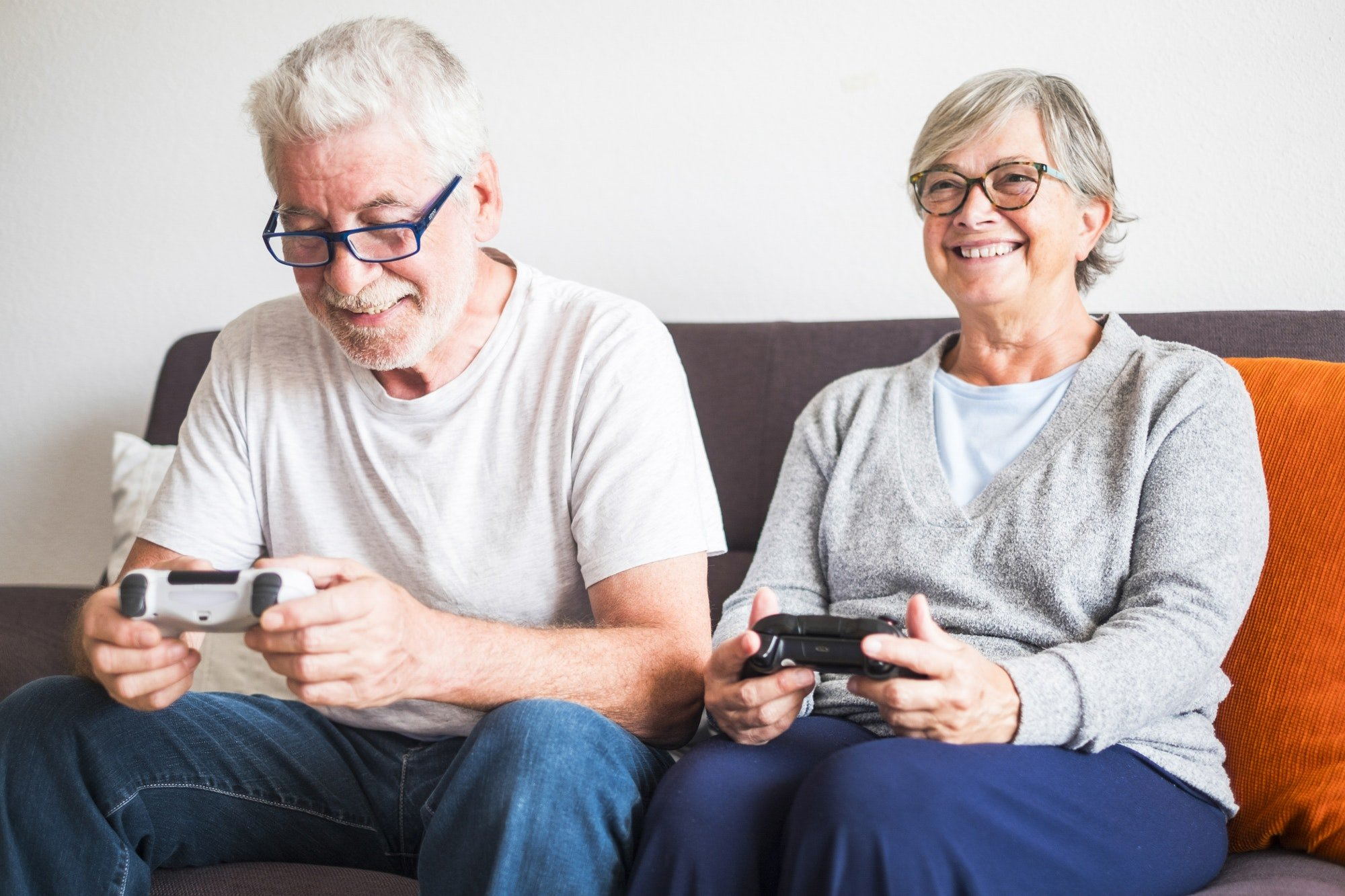 couple of seniors and mature people looking and the tv and using controllers playing video games