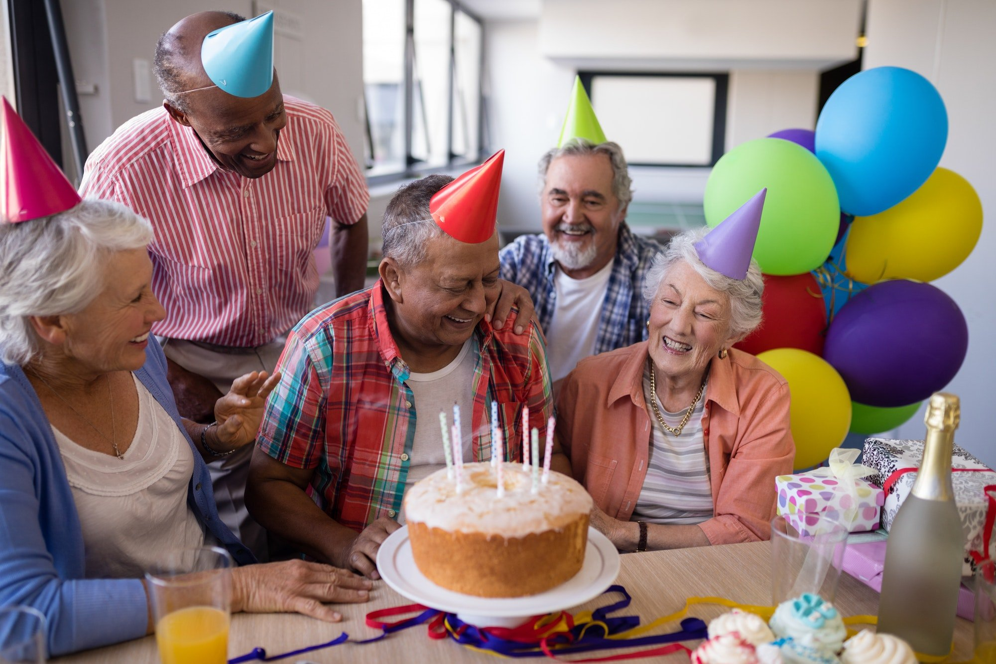 Happy senior friends by birthday cake at party