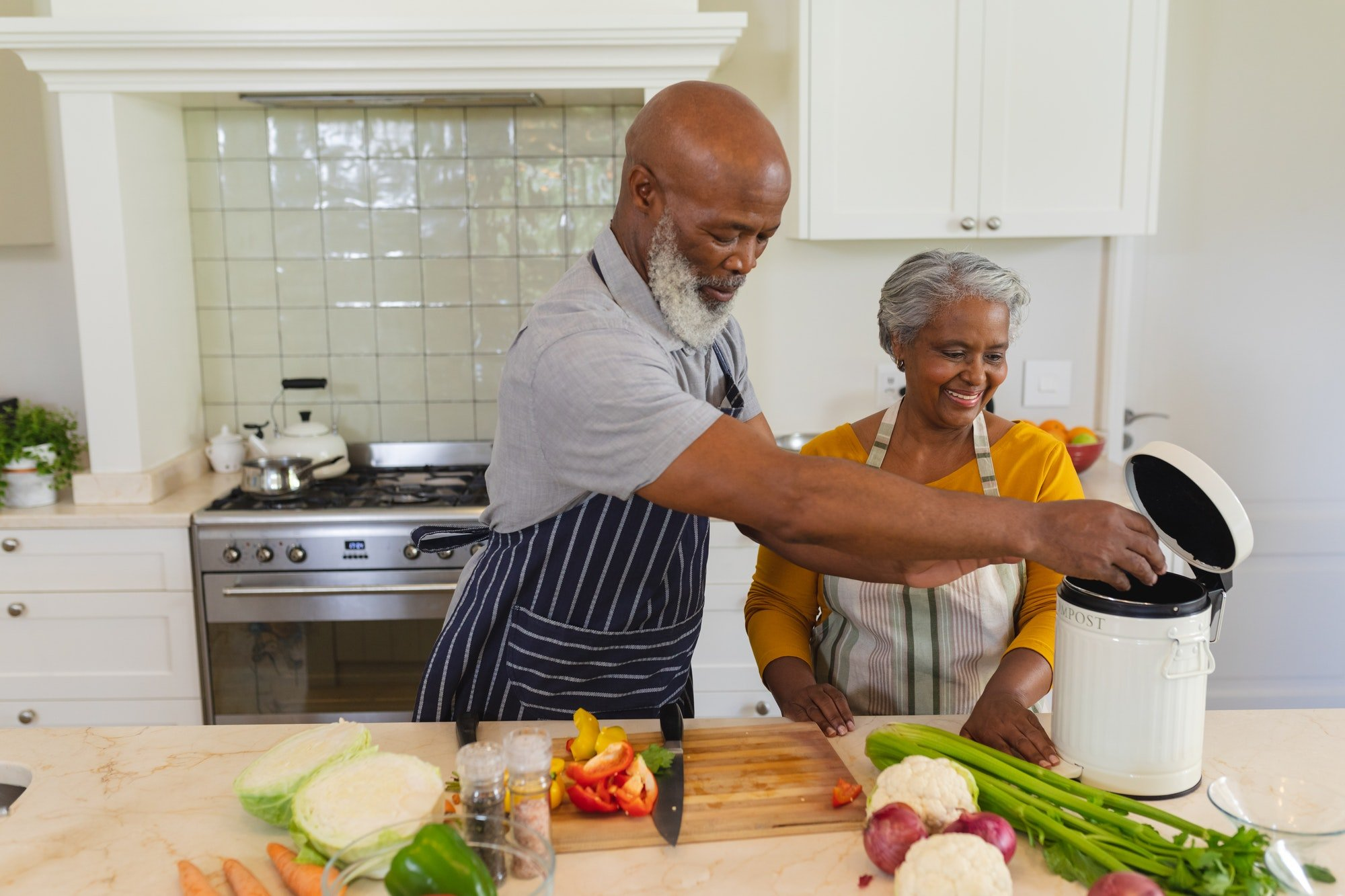 Senior african american couple cooking together in kitchen smiling