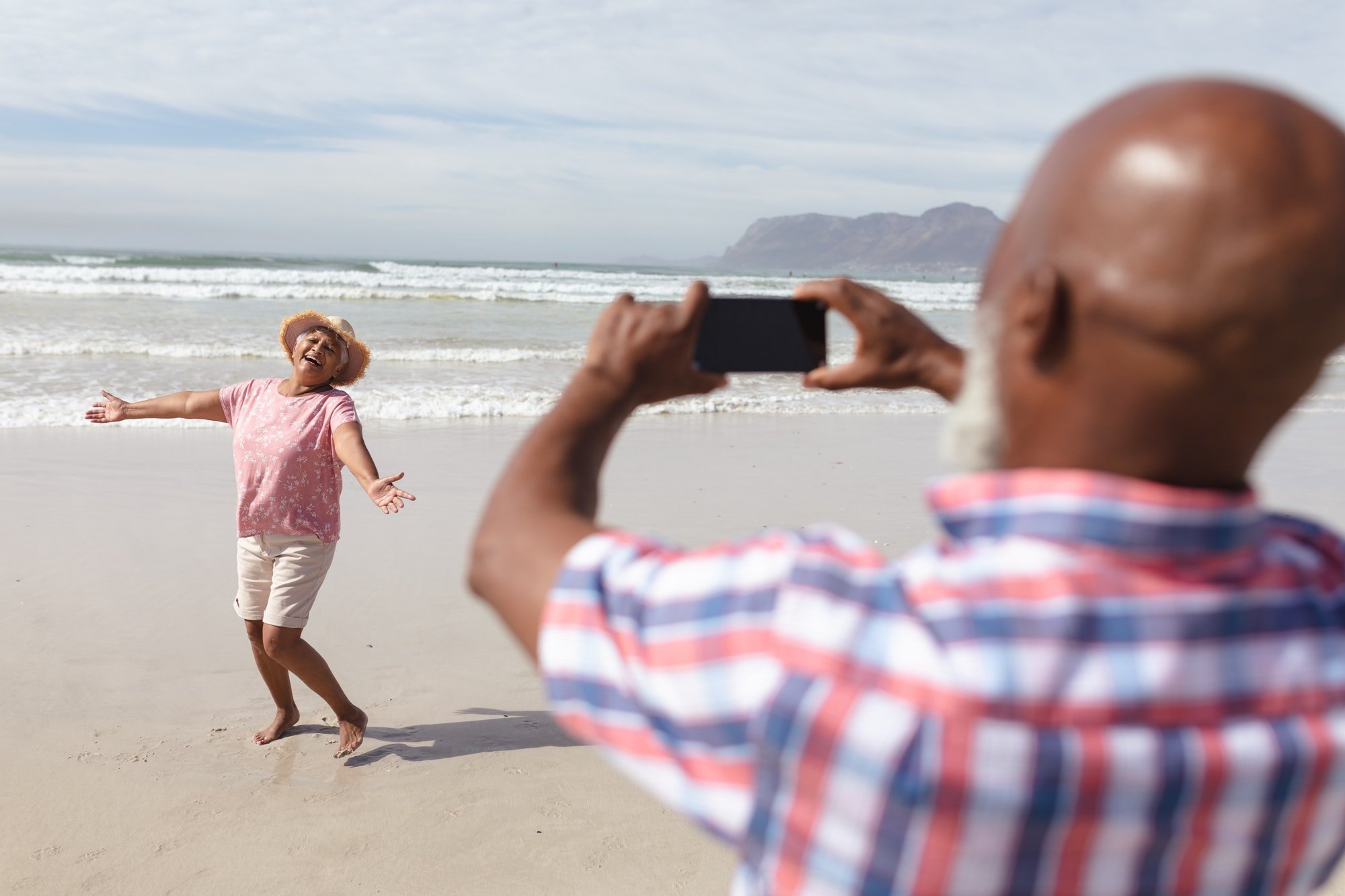 Senior african american man taking a picture of his wife on the beach