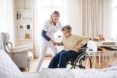 a-health-visitor-helping-a-senior-woman-to-stand-KFBTHXN.jpg