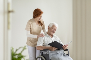 Happy elderly man in the wheelchair reading a book during visit of caregiver at home