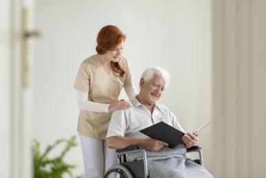 happy-elderly-man-in-the-wheelchair-reading-a-63VJ92L.jpg